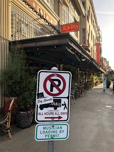 A new Musician Loading By Permit sign outside Al's Den in SW Portland. Celebrate the pilot program's launch outside Dante's (in a loading zone) at 1:15pm on March 15 with a performance from And And And!