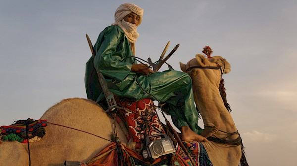 A participant at the Shiriken Festival, which celebrates Tuareg culture, dance and music, in Akoubounou, Niger; camels are integral to the traditional Tuareg way of life and the fest features camel races, desert blues music and even camel dancing, where riders make their camels step to a drumbeat: Photo by Christopher Kirkley