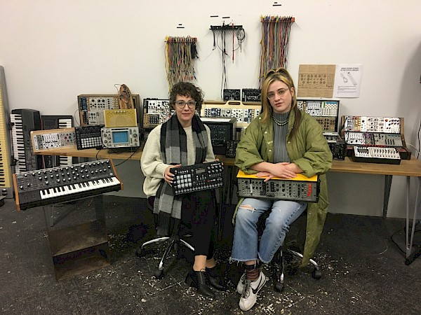 Teacher, artist and Synth Library co-founder Alissa DeRubeis and S1 co-founder Felisha Ledesma with said library, which provides S1 members of all experience levels with hands-on access to modular synthesizers, DJ gear, recording equipment and other electronic instruments