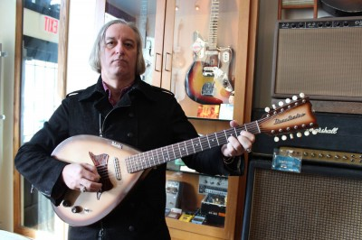 Peter Buck posing with a teardrop-shaped, 12-string Danelectro Bellzouki